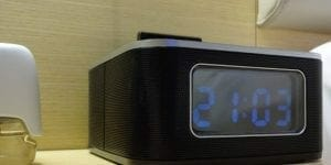 an alarm clock on a nightstand with a camera