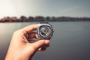 a watch being held with a lake background
