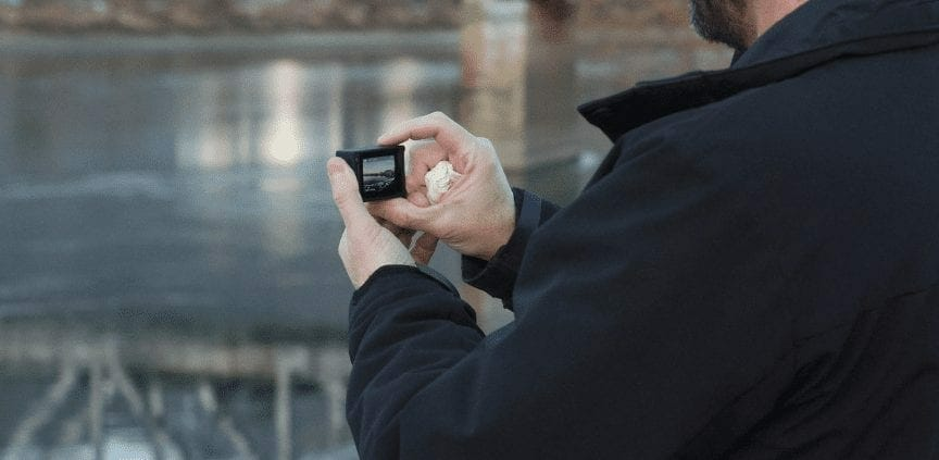 a man in a jacket holding a mini camera